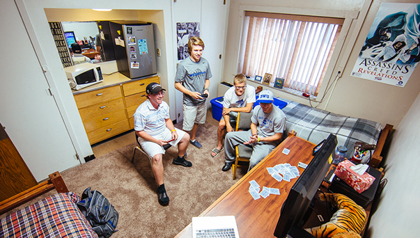 Male college students playing video games in a dorm room