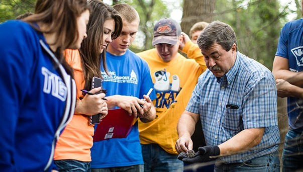 An instructor showing a mouse to a group of students