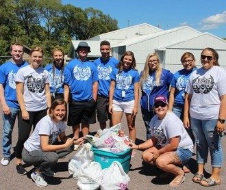 DWU freshmen and upper-classmen pose for a group photo by some of their collection Sunday after the Freshman Food Drive.