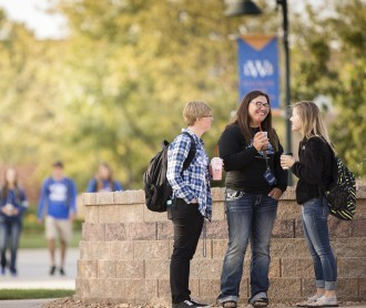 Photograph of three students laughing, drinking coffee by a fountain on campus.