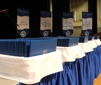 Image of diploma covers stacked on table before Commencement ceremonies begin, 2016.