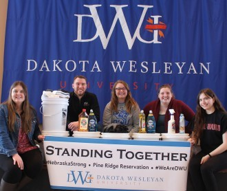 Campus Ministry students pose with supplies for flood buckets.
