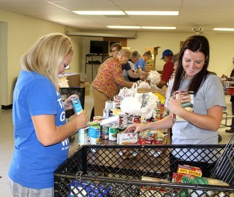 DWU students sort food items during 2015's Freshman Food Drive.