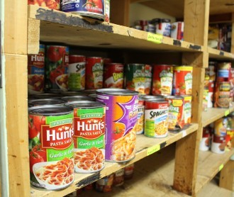 Photo of canned food on shelves in food pantry.