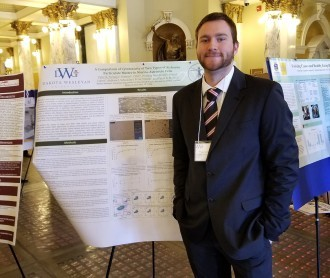 Tyler Fortuna, DWU senior, stands next to his SD BRIN research poster in capitol building in Pierre, SD.