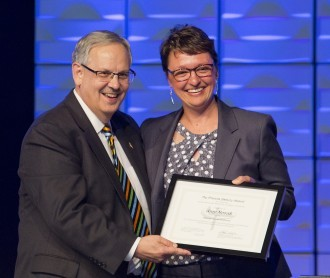 DWU President Amy Novak receives the Francis Asbury Award from Bishop Bruce Ough.