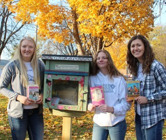 Members of FTO beside a Little Library: Brittany Bergquist, Kiana Kuchta and Emily Brunsing