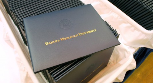 Photo of Dakota Wesleyan University diploma cover, laying on top of others. Taken prior to DWU Commencement 2017.