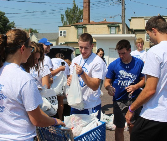DWU students weigh sacks of donated food during food drive.