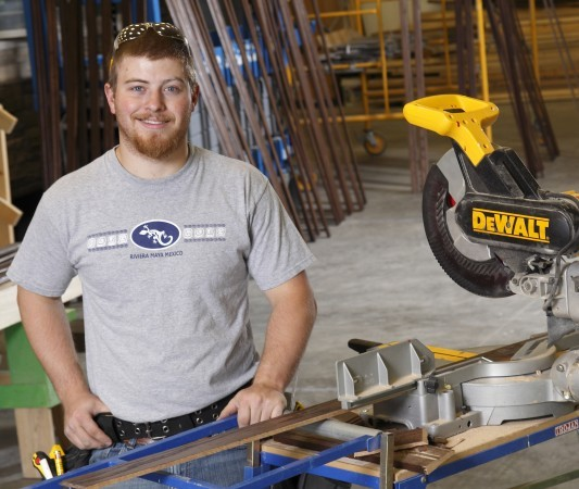 Construction student posing with tools.