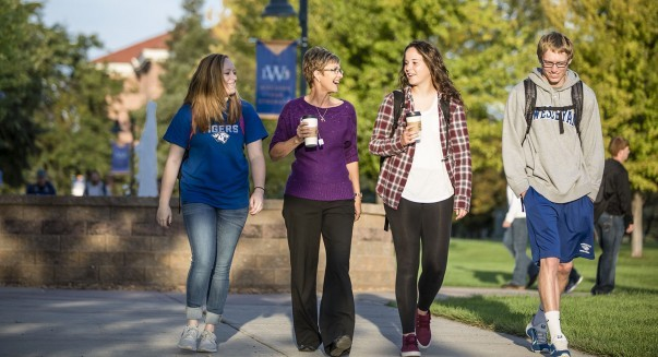 Professor Jerry Luckett walks across campus with students.